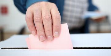 Hand posts vote through ballot box slot