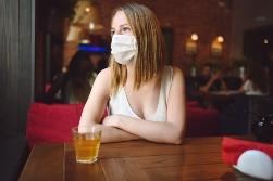 Woman sitting with facemask on in restaurant