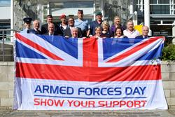 A group of people stand in front of an official building holding a flag saying Armed Forces Day Show Your Support