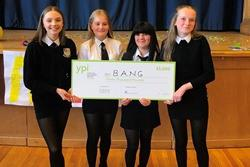 A group of four school pupils hold a large presentation cheque