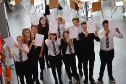 Group of students holding up their exam result papers