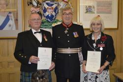 Captain Gerald Maitland-Carew presents British Empire Medals to Brian McLeod and Jessica Troughton