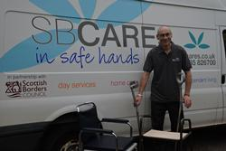 Man in SB Cares uniform standing in front of a SB Cares van with a wheelchair and walking frame