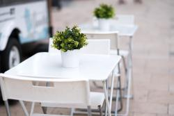 White plastic and chrome tables and chairs outside on a pavement