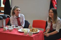 Two senior school pupils sit in front of a table