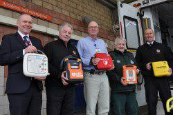 Representatives holding portable defibrillators in front of A&E department