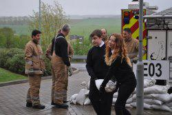 Pupils carrying sandbags outside with firemen