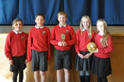 Five schools pupils hold a cup they have won