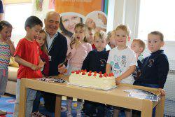 Young children and Councillor Sandy Aitchison round a large cake