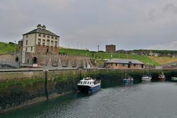 Eyemouth harbour, building with harbour wall and boat in the water