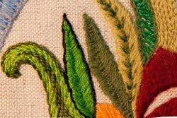 section of tapestry showing stitched leaves