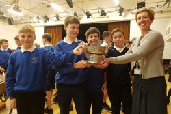 Four school pupils are being presented with a trophy by a taller woman