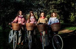 four young women standing with their bicycles