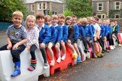 Primary school children sitting astride barriers showing their shoes