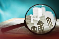 Magnifying glass looking at houses