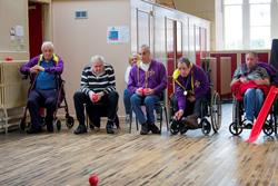 group of men in wheelchairs are playing the sport, boccia