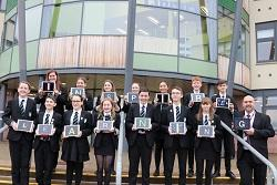 Group of pupils with iPad's standing outside school building