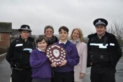Primary pupils, police officers and council officials with an award