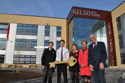 Staff, councillor and pupil outside a new school building