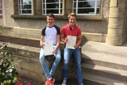 Two students still on a wall holding envelopes containing their exam results