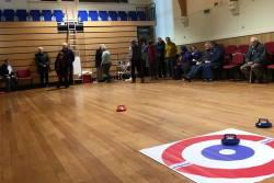 A group of people stand around the edge of a village hall playing a game of new age kurling