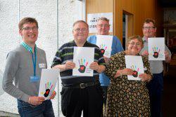 A group of five people hold up leaflets that have an image of a hand on them