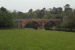 old bridge in the countryside surrounded by trees and fields