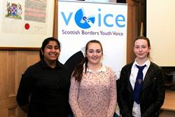 Three young women stand in front of a banner promoting Scottish Borders Youth Voice