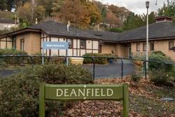Entrance sign to Deanfield Crae Home with building in background