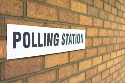 Polling station sign on brick wall