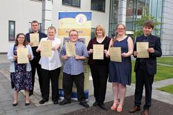 A group of eight young people standing holding certificates
