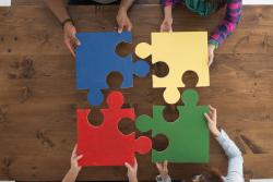 four people round a wooden table holding large jigsaw puzzle pieces