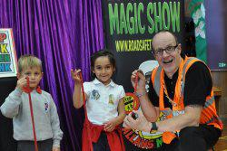 Primary school pupils and magician holding rope for a magic trick