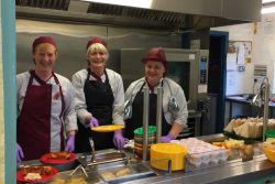 Three dinner ladies at a school canteen serving hatch