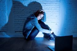 scared young woman sitting on the floor in front of a laptop