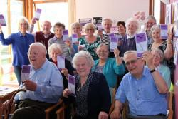 Older people gathered in a room each holding a copy of a leaflet