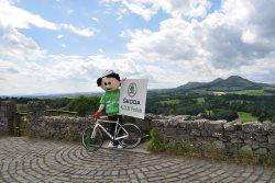 Tour of Britain mascot on a bike overlooking Scott's View