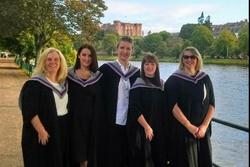 Five women in graduation robes beside a river with trees in the background