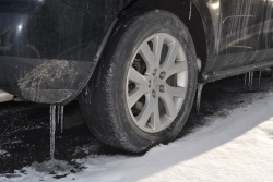 icicles hanging from rear bumper and rear car tyre on snowy road