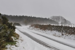 Heavy snow on a country road with tyre tracks showing
