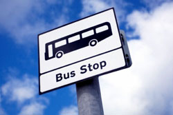 Bus stop sign with blue sky and clouds in the background.