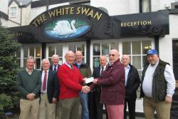 A group of older men stand in front of the White Swan hotel in Duns