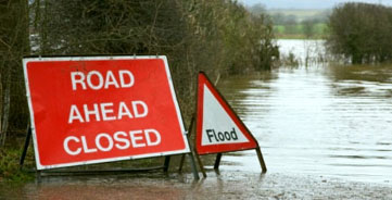 'Road ahead closed' and 'flood' signs in front of a flooded road.