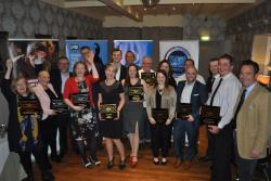 A group of award winners hold their award plaques