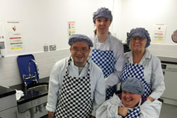 A group of four people in white uniforms and blue checked catering aprons.
