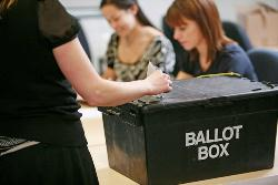 Person posting ballot into box
