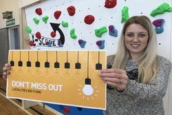 Woman holds yellow sign reading 'don't miss out; localities bid fund'